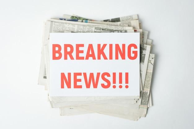 Mucchio di giornali freschi sul tavolo bianco con scritta rossa breaking news in cima