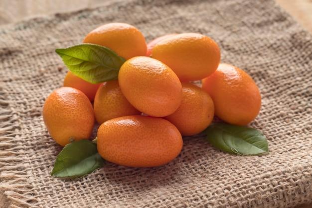 Pila di freschi e gustosi frutti di kumquat su tela di sacco, primo piano