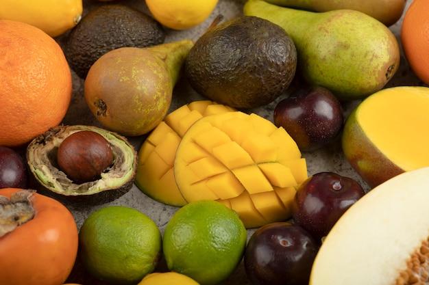 Pila di frutta fresca intera composizione sulla superficie in marmo.