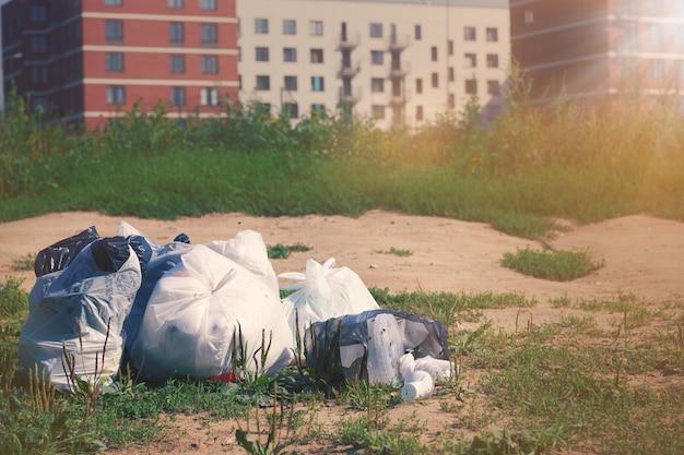 Pila di pacchetti di immondizia su un terreno contro il multi condominio sfocato. rifiuti di plastica. concetto di problema di riciclaggio dei rifiuti e smaltimento dei rifiuti.