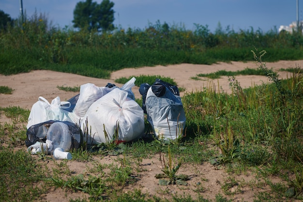 Pila di pacchi di immondizia su un terreno. rifiuti di plastica. concetto di problema di riciclaggio dei rifiuti e smaltimento dei rifiuti.