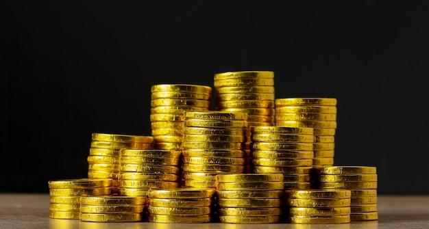 Accumula monete d'oro su sfondo nero e concetto di risparmio futuro