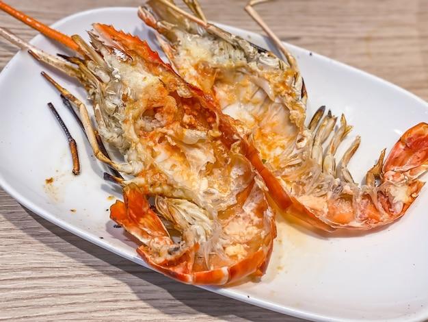 Pila di gusci di gamberi di fiume gigante alla griglia sul piatto bianco sul tavolo di legno come sfondo. popolare cibo tailandese