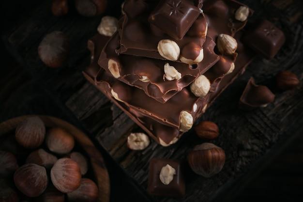 Mucchio di cioccolato al latte nocciola e noci su fondo di legno scuro. vista dall'alto