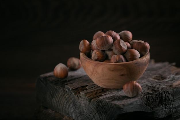 Mucchio di nocciole nocciola in una ciotola di legno su uno sfondo di legno scuro. noci fresche nel loro guscio.