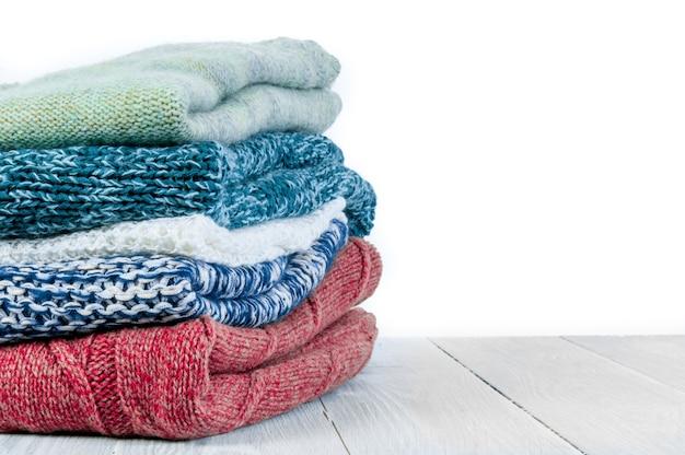 Pila di vestiti invernali lavorati a maglia su fondo di legno, maglioni, maglieria, spazio per il testo. concetto di primavera.