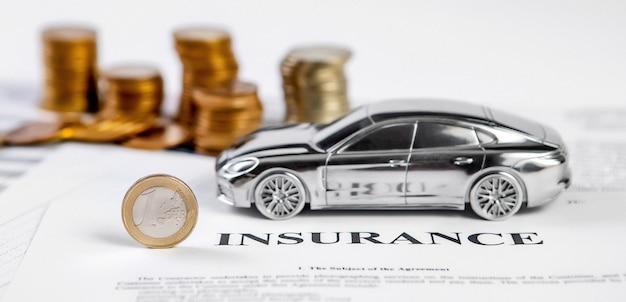 Mucchio di monete di denaro e macchinina. concetto di assicurazione, prestito, finanza o acquisto di auto.