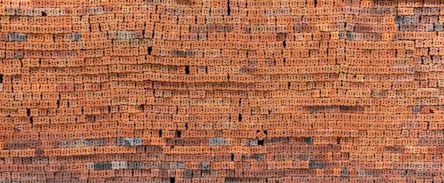 Mucchio di nuovo strato di mattoni rossi preparato per il fondo di struttura della costruzione.