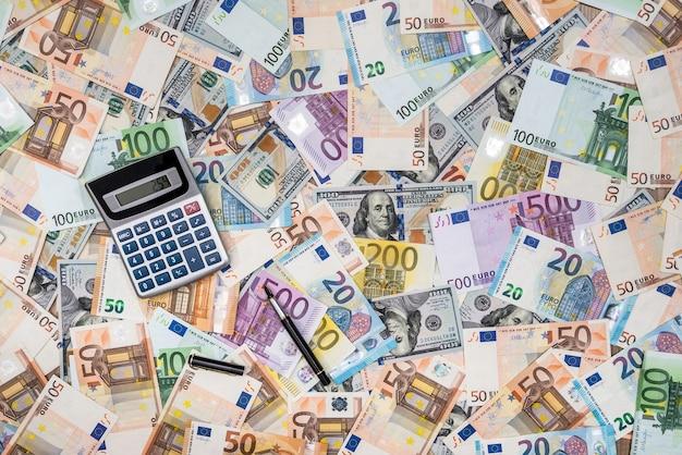 Mucchio od banconote in dollari ed euro con la calcolatrice