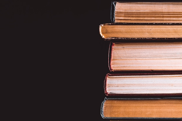 Pila di vecchi libri su sfondo nero