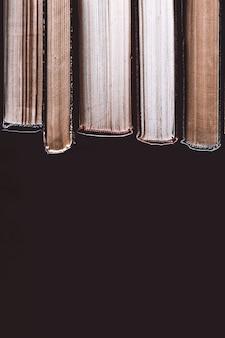 Pila di vecchi libri su una superficie nera