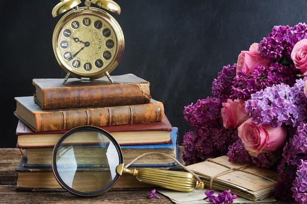 Pila di vecchi libri con sveglia e un bicchiere di ricerca