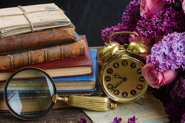 Pila di vecchi libri con sveglia, specchio e fiori