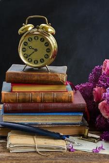 Pila di vecchi libri con sveglia, specchio e vecchia posta