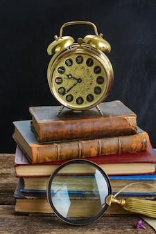 Pila di vecchi libri con sveglia