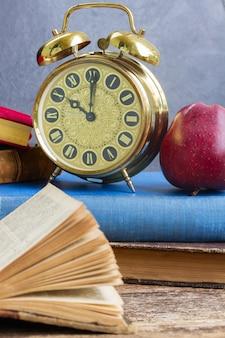 Pila di libri antichi con sveglia antica e mela