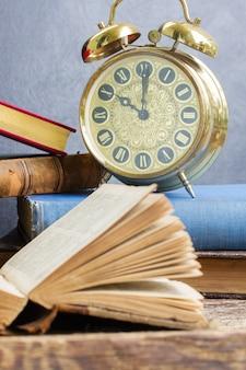 Pila di libri antichi con sveglia antica