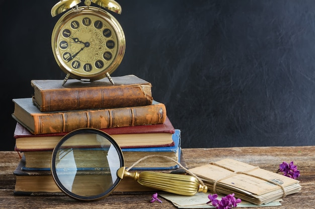 Pila di vecchi libri con sveglia vintage uno specchio