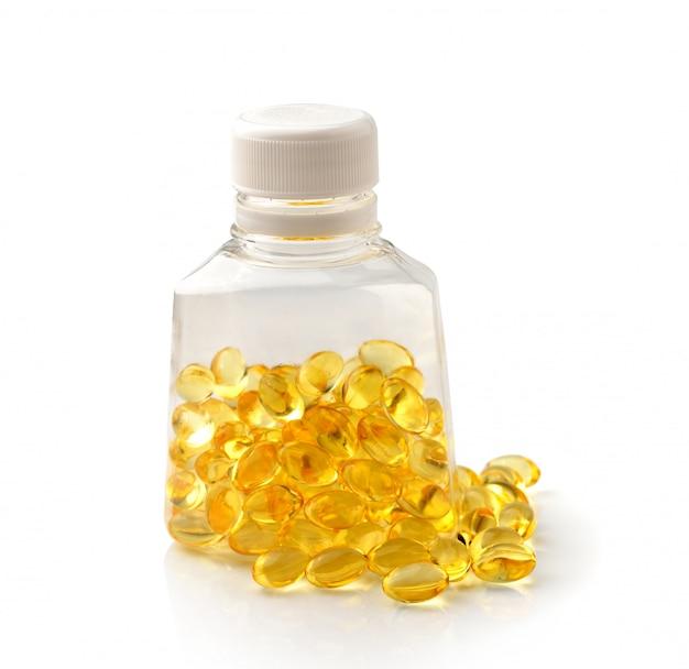 Mucchio di omega 3 capsule di olio di pesce che si rovesciano da una bottiglia su bianco