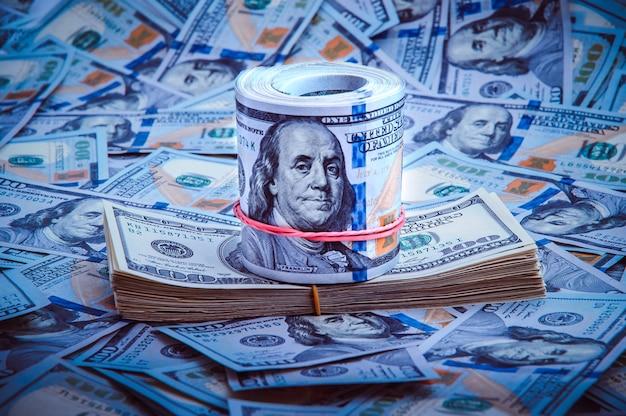 Un mucchio di cento banconote degli stati uniti con i ritratti del presidente. contanti di centinaia di dollari