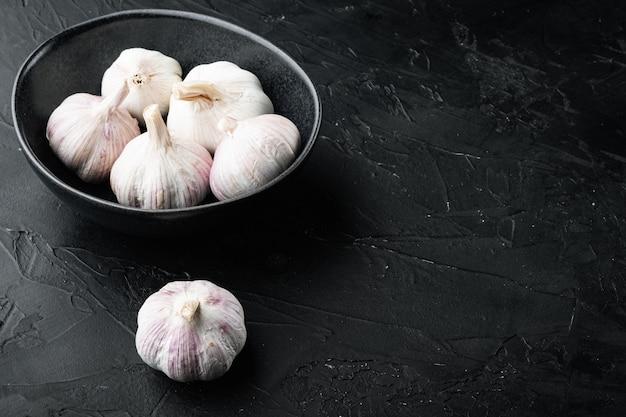 Pila di set di aglio di fattoria biologica, nella ciotola, sul nero