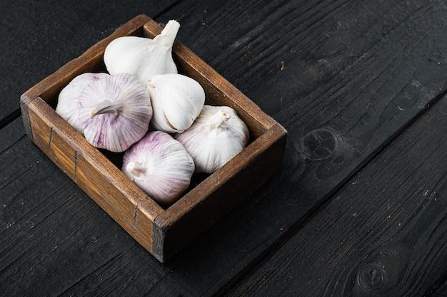 Pila di aglio di fattoria biologica insieme, in una scatola di legno, sul tavolo di legno nero