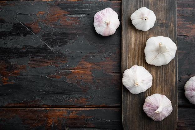 Mucchio di set di aglio fattoria biologica, sul tagliere di legno, sul vecchio tavolo in legno scuro