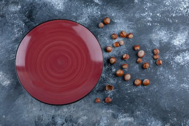 Pila di nocciole sgusciate biologiche con targhetta rossa vuota.