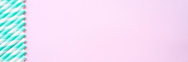 Mucchio di cannucce bianche e verdi a strisce di carta per la festa sulla superficie rosa