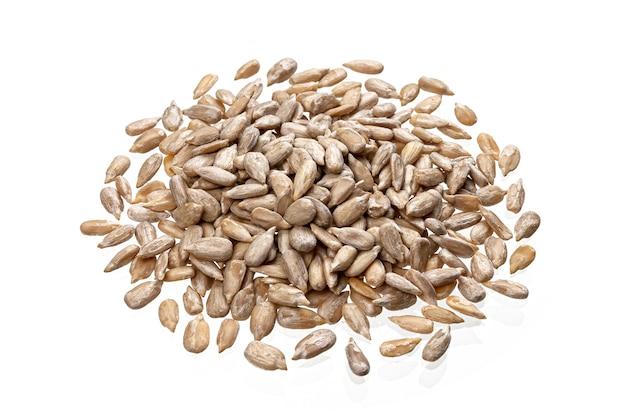 Pila di semi di girasole sbucciati isolati sul tavolo bianco