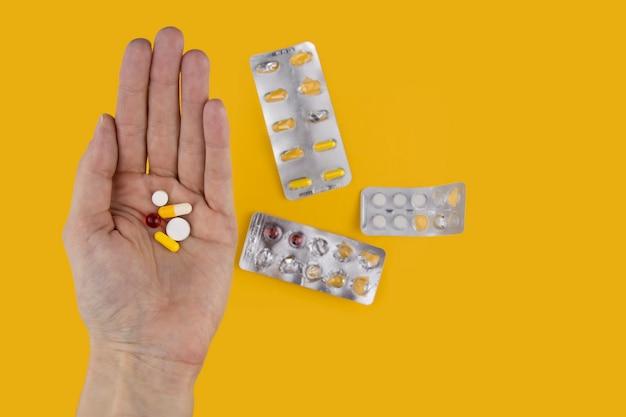 Un mucchio di pillole in mano su un muro giallo. dose di farmaci.