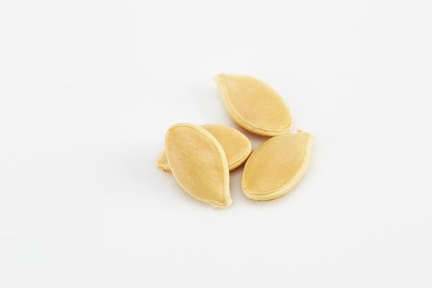 Pila di semi di zucca crudi sulla superficie bianca