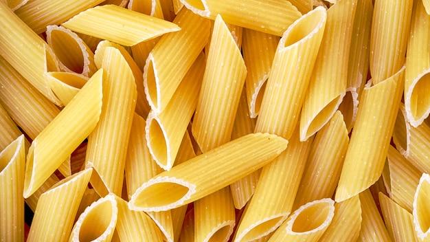 Un mucchio di pasta di penne italiana integrale cruda, vista dall'alto. modello di maccheroni. sfondo di cibo