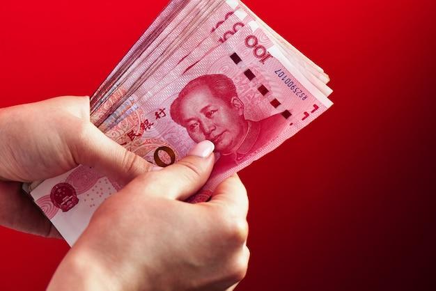 Un mucchio di banconote rmb di yuan cinese denaro in una mano femminile su un rosso