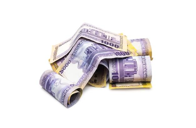 Un mucchio di mille banconote taka bangladesh arrotolate sparse su uno sfondo bianco isolato