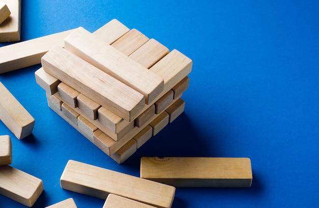 Un mucchio di blocchi di legno sparsi su sfondo blu. gioco di costruzione. la torre spezzata.
