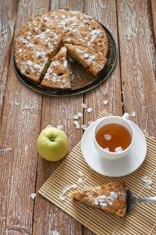 Mucchio di piccoli pancake fatti in casa con miele, tazza di tè e nido d'ape sul tavolo di legno