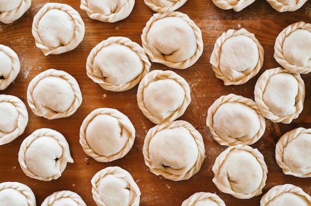 Pila di piccoli gnocchi crudi fatti in casa con carne sul tavolo della cucina. cucina russa tradizionale nazionale. fallo da solo. vista dall'alto, piatto
