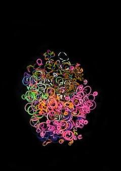 Pila di piccoli elastici rotondi colorati per realizzare braccialetti con telaio arcobaleno isolati su sfondo scuro