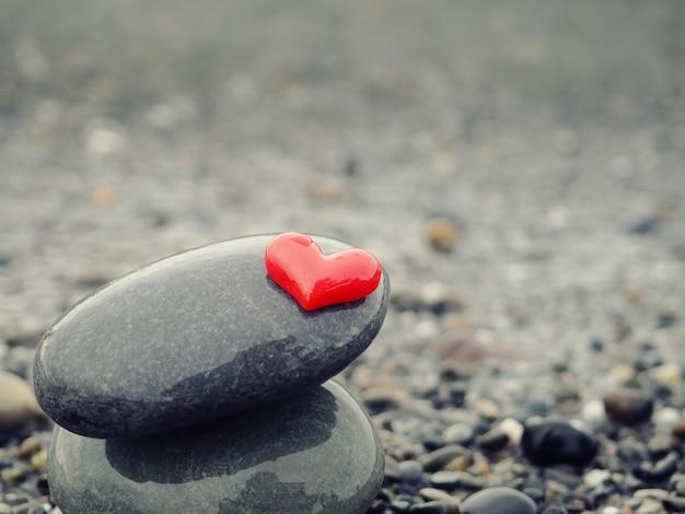Un mucchio di pietre in riva al mare, cuore rosso in alto, relax zen.