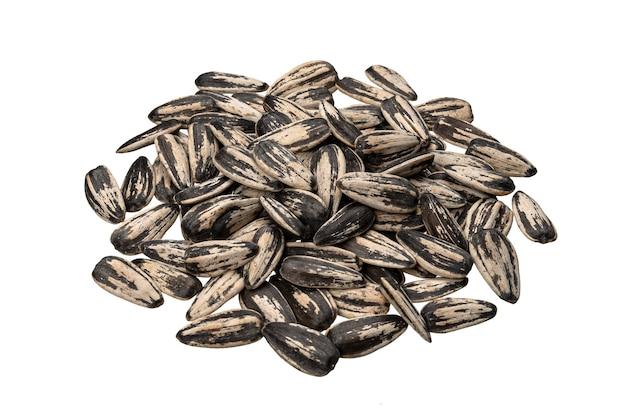 Pila di semi di girasole a strisce isolato sul tavolo bianco