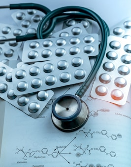 Mucchio delle pillole delle compresse in blister e stetoscopio d'argento del di alluminio sul manuale. industria farmaceutica. uso di droghe in ospedale. assistenza sanitaria.