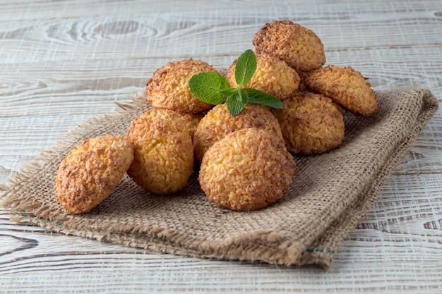 Mucchio dei biscotti saporiti della noce di cocco sulla tavola di legno bianca Foto Premium