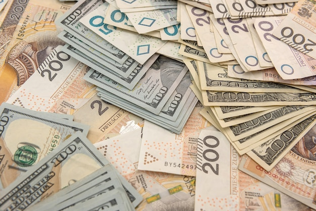 Mucchio di banconote in dollari statunitensi e zloty polacchi come sfondo. investimento