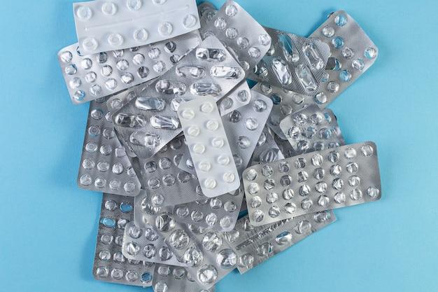 Un mucchio usato blister di pillole su sfondo blu. pacchetti di blister medici aperti e vuoti senza vista dall'alto di pillole. concetto medico e sanitario.