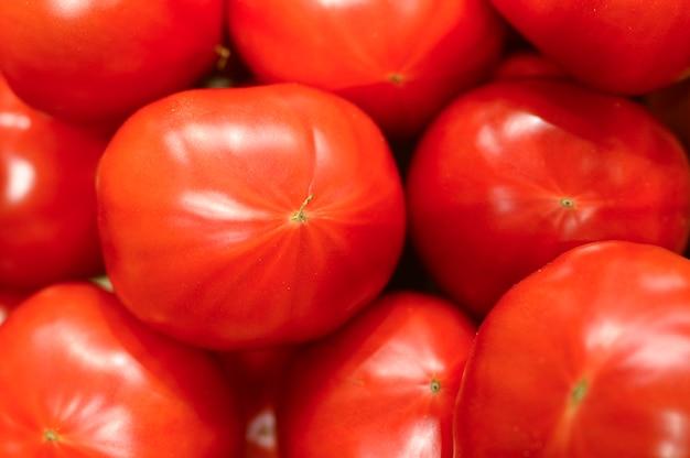 Mucchio di pomodori rossi grandi di verdure come sfondo