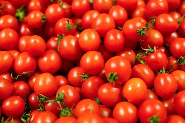 Un mucchio di mini pomodori rossi delle verdure come fondo strutturato