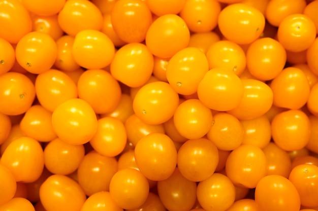 Mucchio di verdure mini pomodori gialli come sfondo