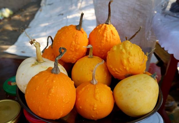 Pila di vivaci zucche di colore giallo e arancione che vendono al mercato