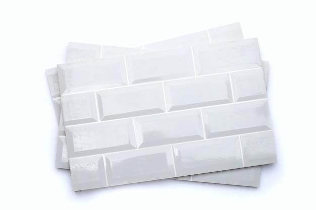 Pila di piastrelle da parete su sfondo bianco.